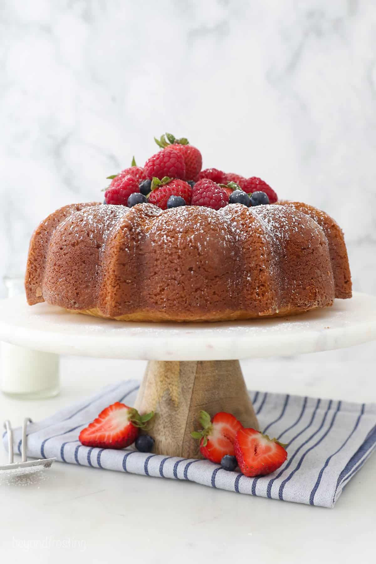A pound cake on a cake platter topped with strawberries, blueberries and powdered sugar