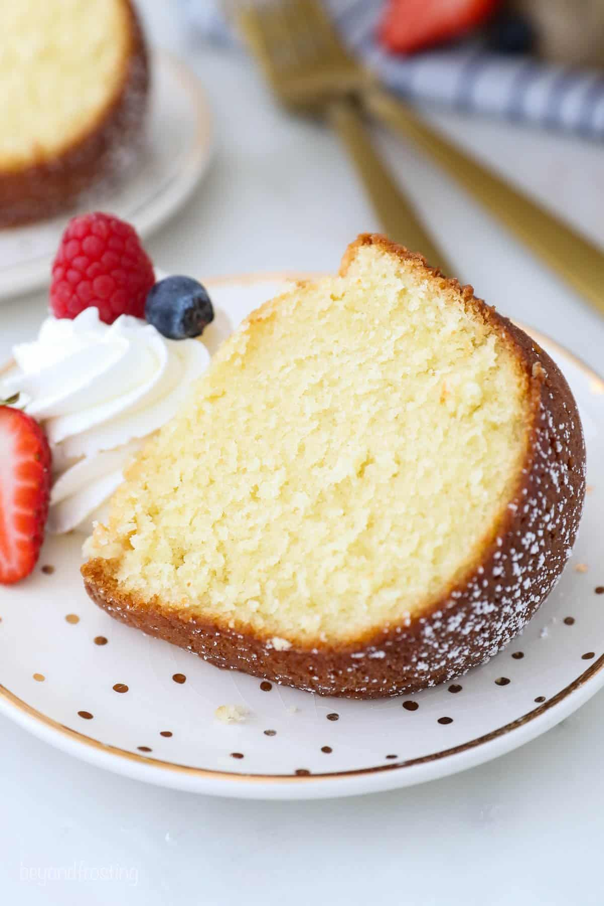 A slice of pound cake on a plate next to a dollop of whipped cream and fresh berries