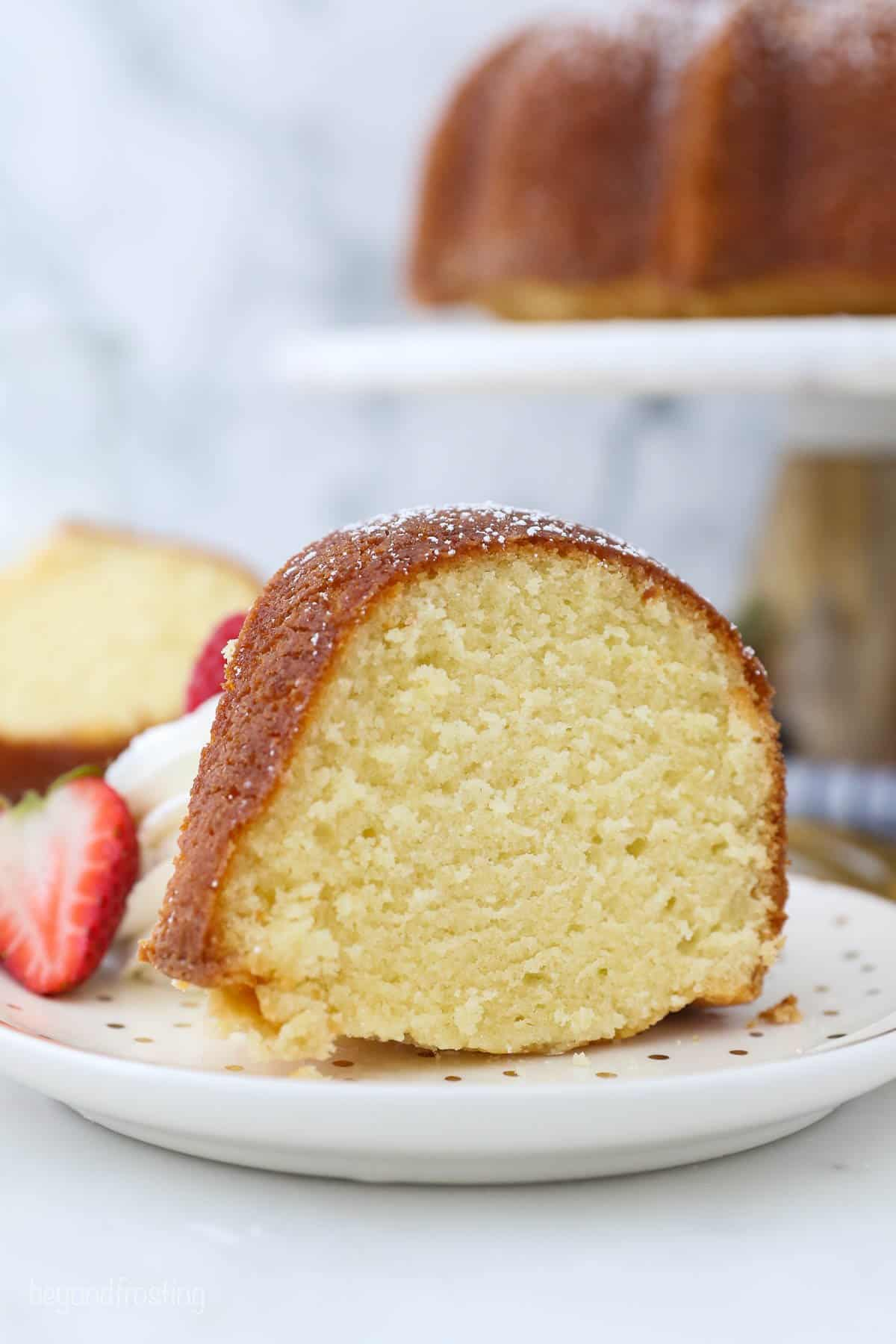 A piece of homemade pound cake sitting on a plate with strawberries and cream