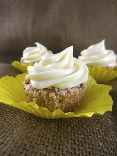Three Gluten-Free Carrot Cake Cupcakes topped with a vanilla cream cheese frosting.