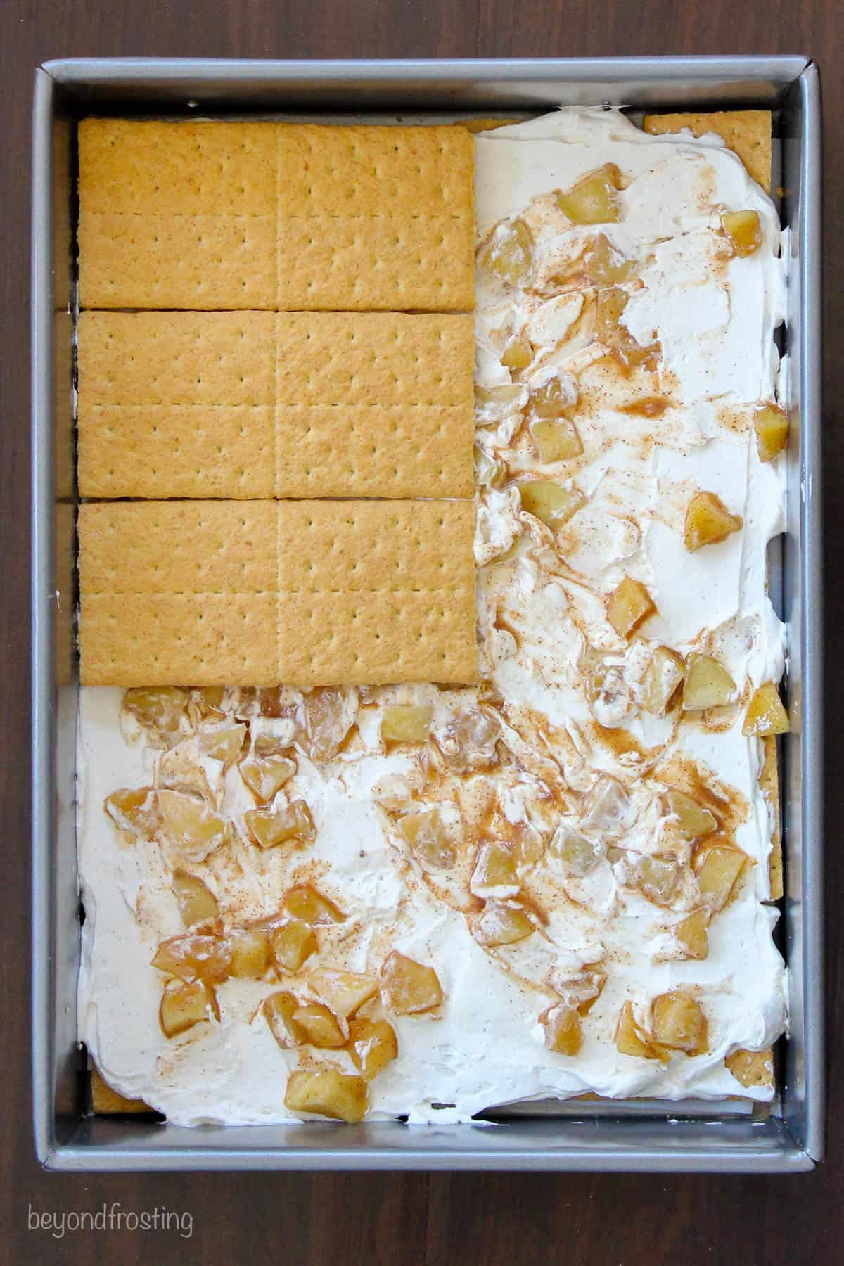 graham crackers being layered over apple pie filling