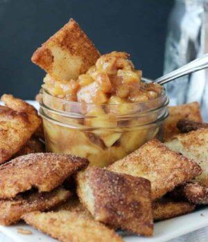 A jar of apple pie dip on a plate full of cinnamon sugar pie crust chips
