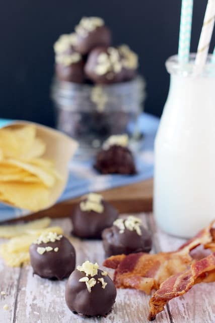 Bacon Potato Chip Truffles on a counter next to a glass of milk, strips of bacon, and a bag of potato chips