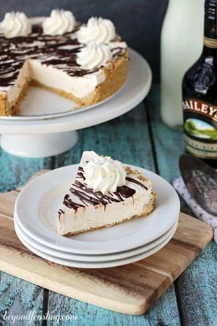 A slice of bailey's spiked ice cream cake topped with whipped cream on a white plate
