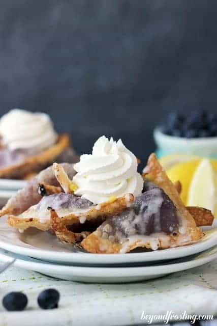 These blueberry cheesecake wontons are filled with fresh blueberry and topped with cream.