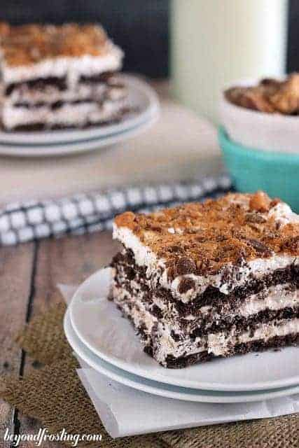 A slice of chocolate and butterscotch pudding layered icebox cake topped with crushed butterfingers
