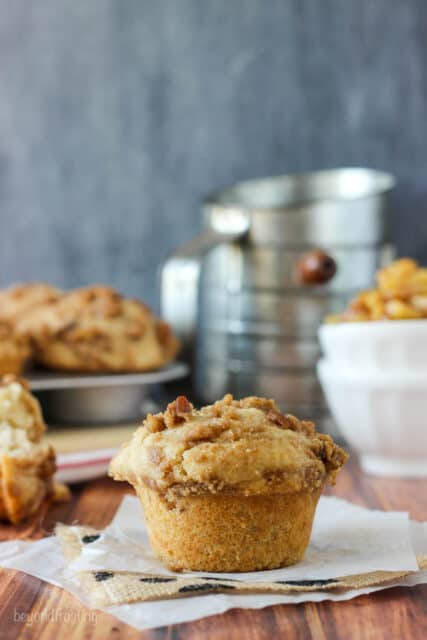 A single apple pie muffin on a table with a full muffin tin in the background