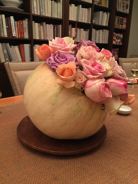 A flower arrangement in a gourd on a dining room table