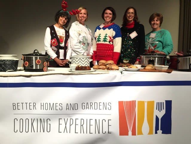 A group of food bloggers in holiday attire posing behind a demo table at BHG Cooking experience event