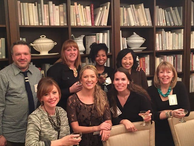 A group of food bloggers posing in front of a bookcase of dishes and books