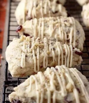 5 Cranberry Maple Walnut Scones resting on a wire cooling rack.