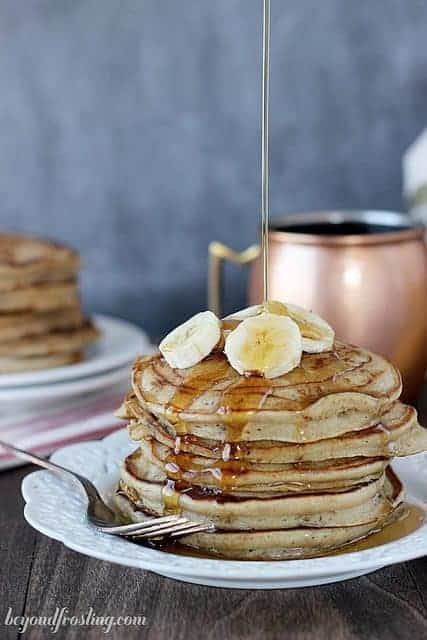 A stack of Peanut Butter Pancakes drizzled with maple syrup and topped with banana slices.