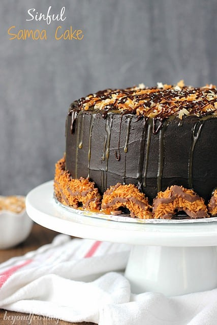 Sinful Samoa Cake. Dark chocolate cake with a toasted coconut and caramel cream cheese layer. Frosted with a fudge dark chocolate frosting and topped with toasted coconut and drizzled with caramel and more chocolate.