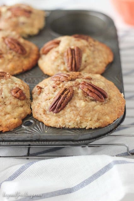 Close-up of Bakery Style Cinnamon Pecan Muffins in a tin with one removed