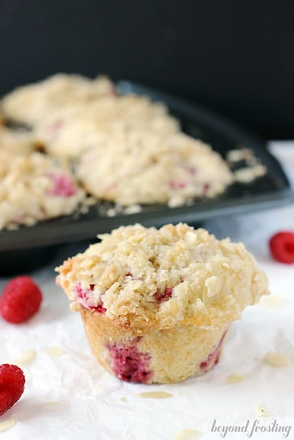 Lemon Raspberry Almond Muffin on a napkin in front of the tin of muffins