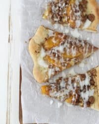 This Peach Streusel Pizza is a cinnamon and sugar loaded pizza dough covered in peaches, walnuts and a vanilla glaze.
