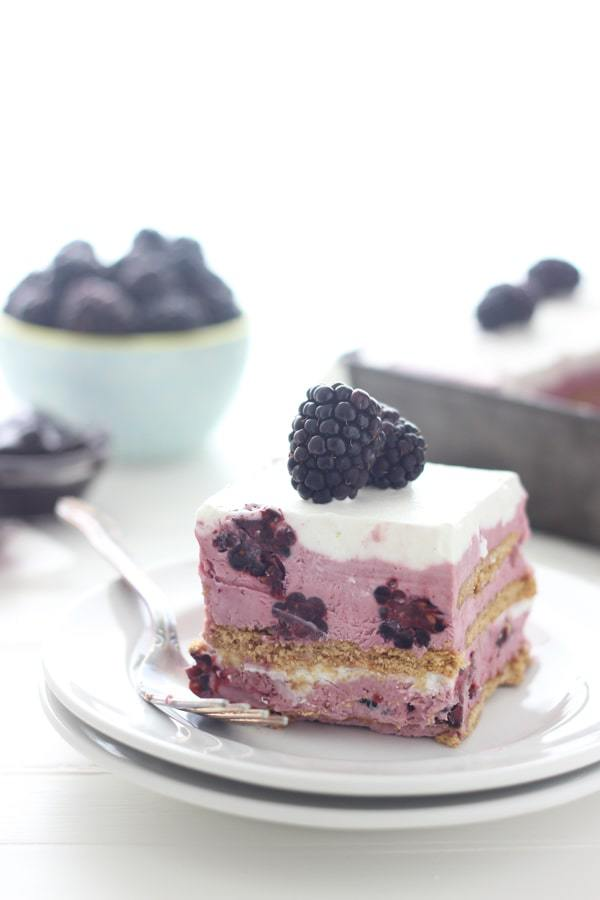 A white plate with a slice of blackberry ice cream cake is topped with 3 fresh blackberries