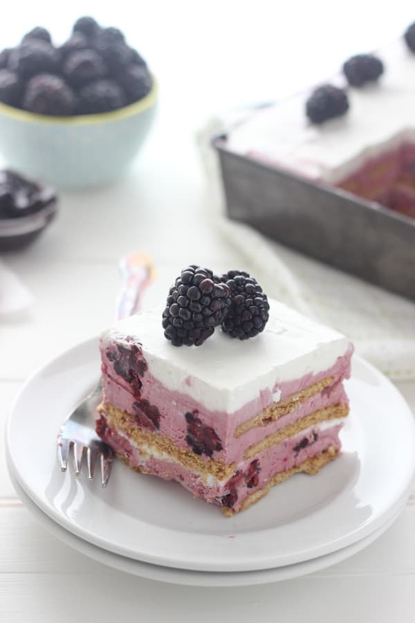 A gorgeous slice of blackberry ice cream cake that is layered with graham crackers and fresh berries.