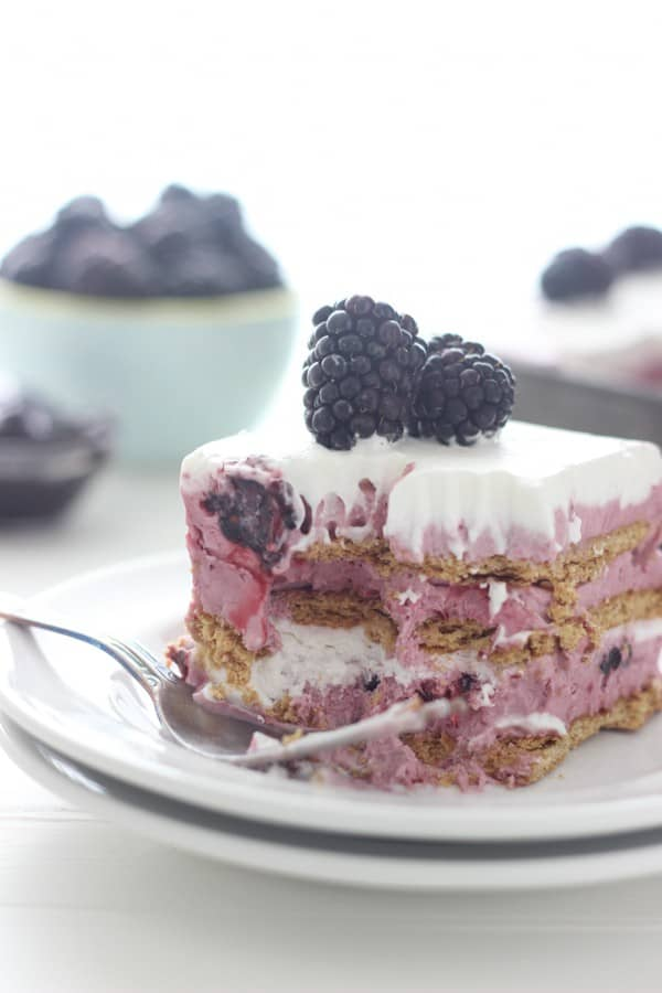 A slice of blackberry icebox cake on a double stacked white plate. It has a few bites taken out of it showing the inside of the cake, and a silver fork is resting on the plate.