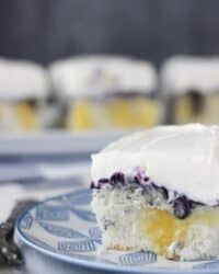 This Blueberry Cheesecake Poke Cake is a fresh vanilla cake filled with cheesecake pudding and a sweetened blueberry sauce. Best of all, it is topped with a cream cheese whipped cream.