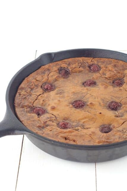 Large skillet baked brownie filled with cherries. Top this Black Forest Skillet Brownie with chocolate whipped cream
