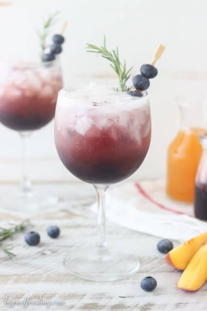 This Blueberry Peach Spritzer is an easy way to impress your friends with a homemade cocktail. A simple blueberry syrup is combined with peach juice concentrate and mixed with prosecco or seltzer. It can be garnished with additional blueberries or rosemary.