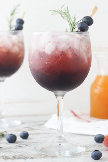 This Blueberry Peach Spritzer is the best summer cocktail!! First I prepared a simple, fresh blueberry syrup which is combined with peach juice concentrate and topped off with prosecco. Now if you are looking for a virgin drink, this also works great with a little bit of seltzer as well.