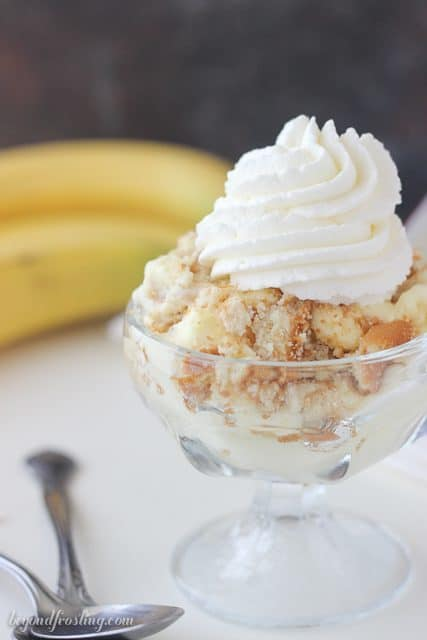 Close up of Banana pudding in a glass cup topped with Nilla wafers and whipped cream