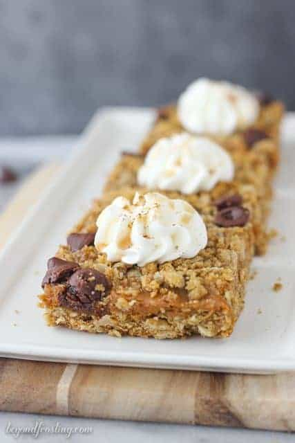 These gooey Caramel Pumpkin Pie Bars layered with a brown sugar oatmeal crust, pumpkin caramel filling and caramel filled chocolate chips.