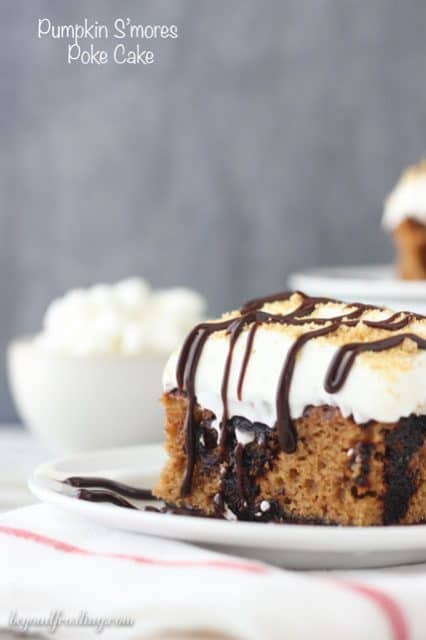 This Pumpkin S'mores Poke Cake is a pumpkin cake with a chocolate graham cracker crust. It is soaked with chocolate pudding and topped with a marshmallow whipped cream.