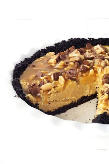 This Snicker Peanut Butter Oreo Pie will make you swoon. An Oreo crust is filled with smooth peanut butter filling and topped with Snickers, peanuts, caramel sauce and chocolate chips.