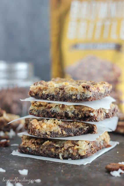 Gooey Brownie Brittle Toffee Seven Layer Bars. The Brownie Brittle crust is layered with coconut, toffee, chocolate and walnuts.