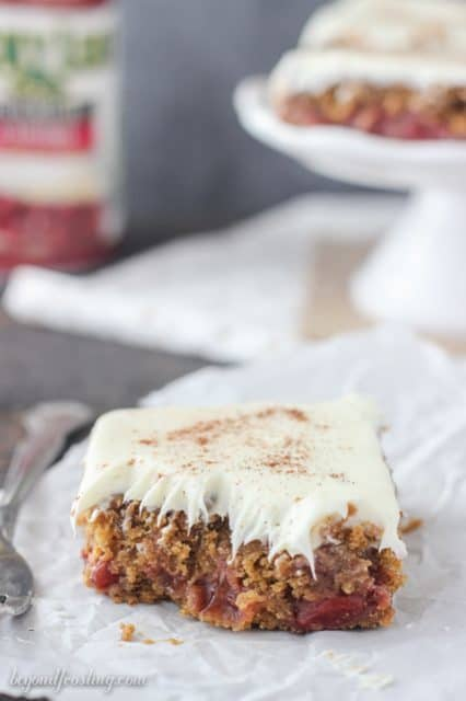 Gooey Gingerbread Cake Bars with cherry pie filling and vanilla frosting.