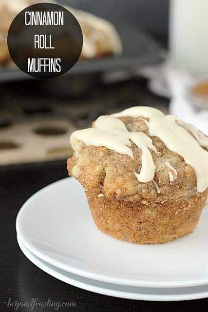 A Cinnamon Roll Muffin drizzled with a vanilla glaze resting atop a white plate.