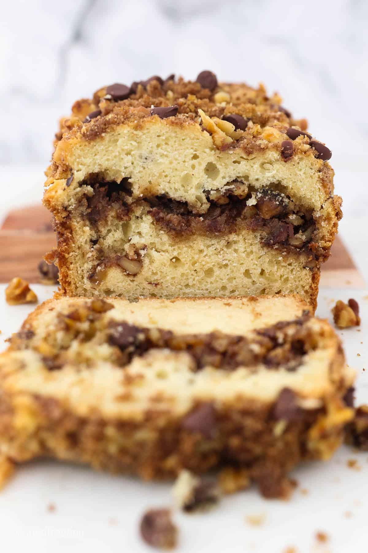 A loaf of sour cream coffee cake with one piece cut and laying in front