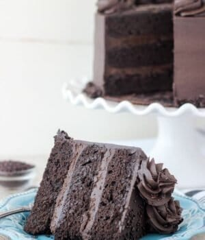 A 3 layer chocolate cake sitting on a dark teal plate. There's a white cake stand in the background with the chocolate cake on top.