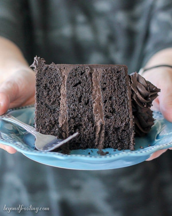 A slice of Guinness Chocolate Cake being held on a plate