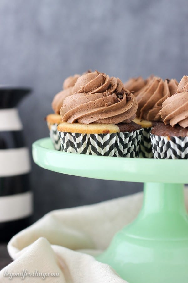 A teal cake stand with Irish Cream cupcakes with chocolate frosting and a black and white striped pitcher in the back