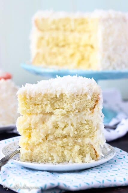This Coconut Custard Cake is layers of coconut cake, with a coconut custard filling and finished with a cream cheese icing. This from scratch recipe will be one you make over and over again.