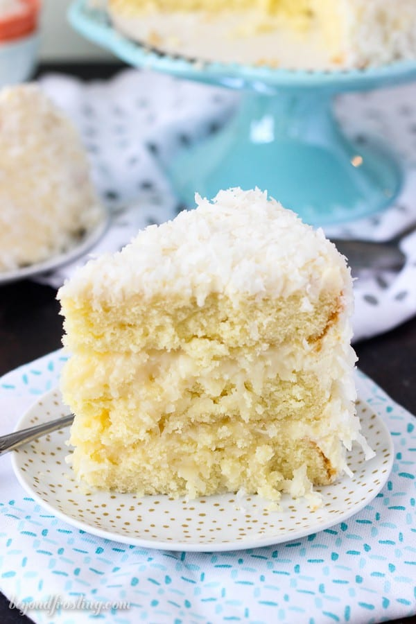 A tall slice of coconut cake on a white and gold polka dot plate