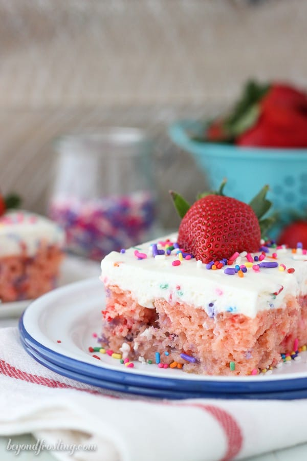 A Piece of Strawberry Funfetti Poke Cake with a Strawberry on Top