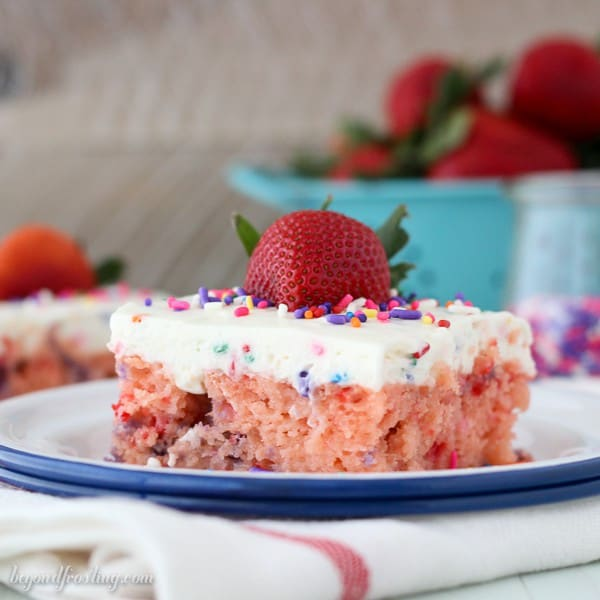 You'll want to dive head first into this Strawberry Funfetti Poke Cake!! This Strawberry cake is drenched in sweetened condensed milk and finished with funfetti whipped cream!