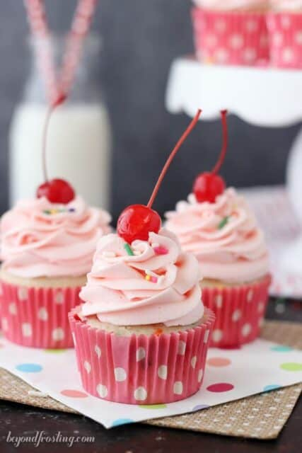 Three Cherry Almond Funfetti Cupcakes in pink cupcake wrappers and topped with a pink cherry almond frosting and a maraschino cherry.
