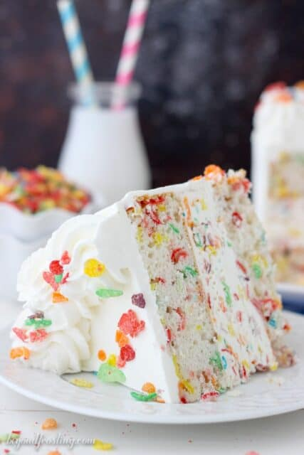 A slice of Fruity Pebbles Ice Cream Cake on a white plate