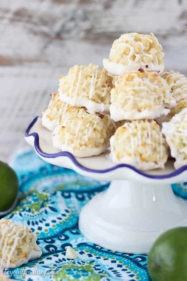 Quick and easy white chocolate coated Coconut Lime Macaroons. Just 7 simple ingredients, these come together in less than 10 minutes. The fresh lime zest is the perfect compliment to this recipe. This is from the cookbook, Out Of The Box Desserts. It is a must-have!