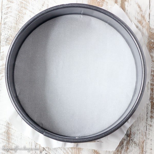 An overhead shot of a springform pan lined with parchment paper