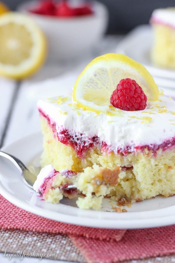 A slice of lemon cake with a layer of raspberry filling, a couple bites are missing