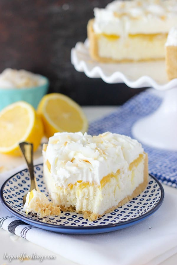 A slice of coconut lemon cheesecake with a bite take out of it on a blue plate