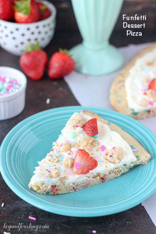 This Funfetti dessert pizza is a giant sprinkle cookie pizza with a marshmallow buttercream and topped with sprinkles and fruit.