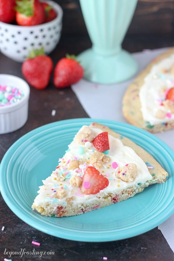 Dessert pizza is so easy! A thick sugar cookie pizza crust loaded with sprinkles. This Funfetti pizza is topped with a marshmallow buttercream, sprinkles and fruit.